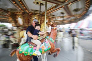 Micah DeBenedetto/Special to the Caller-Times Adolfo Sanchez and grand son Jeremiah Sanchez, 17 months, ride the merry-go-round at the . They were both first time attendants of 2014 Wind Fest on Sunday, April 13, 2014